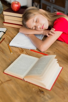 Schulmädchen schläft inmitten von lehrbüchern