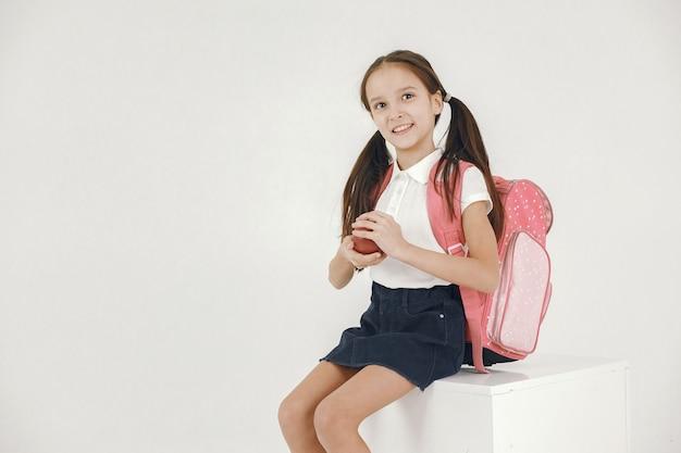 Schulmädchen sitzen auf weißem würfel. mädchen mit rucksack, der apfel auf weiß hält.