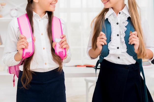 Schulmädchen stehen mit rucksäcken
