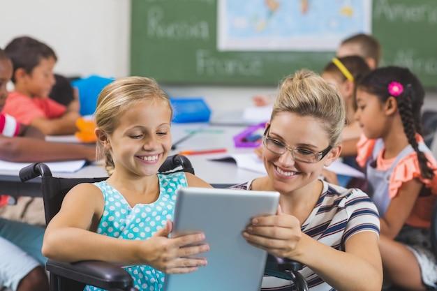Schulmädchen und lehrer mit digitalem tablet im klassenzimmer