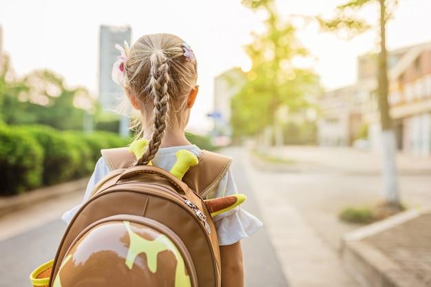 Schulmädchen von hinten mit rucksack zur schule gehen