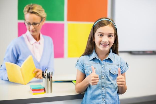 Schulmädchen zeigt daumen hoch im klassenzimmer