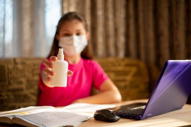 Schulmädchen zeigt kleine weiße flasche mit antibakteriellem spray