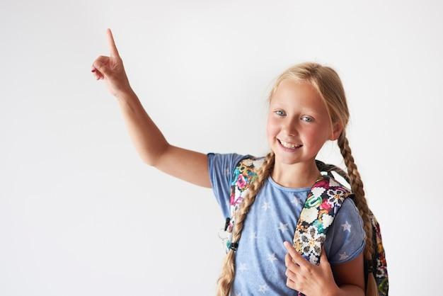Schulmädchen zeigt mit der rechten hand