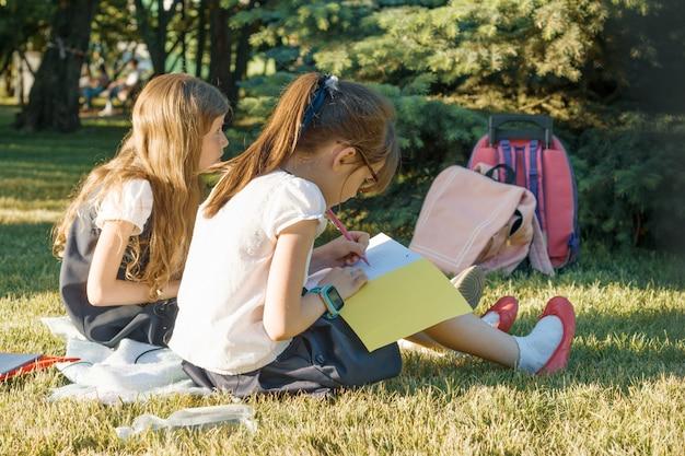 Schulmädchenlernen mit zwei kleinen freundinnen