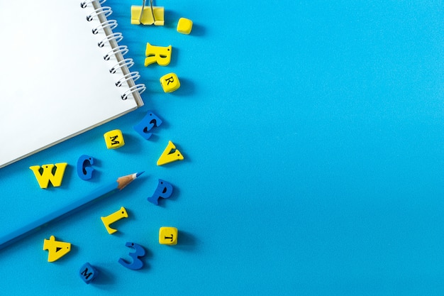 Schulmaterial auf blauem grund. schul- und lehrertageskonzept. hölzerne buchstaben auf dem tisch mit kopienraum.