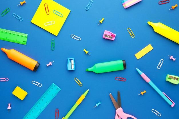 Schulmaterial auf blauem hintergrund. zurück zur schule. flach liegen.