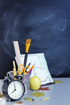 Schulmaterial auf dem hintergrund des lehrergremiums