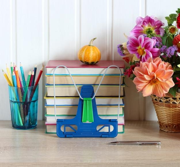 Schulmaterial auf dem tisch ein stapel schulbücher buntstifte und ein blumenstrauß