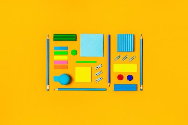 Schulmaterial auf einem gelben.