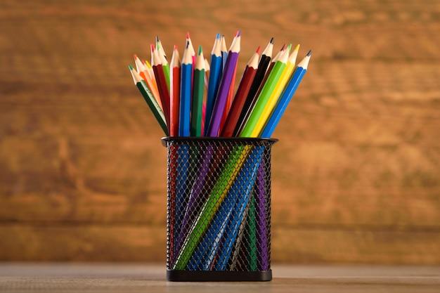 Schulmaterial auf einer warmen, schönen holzwand. buntstifte für kinder in einem schwarzen spindhalter für schreibwaren.