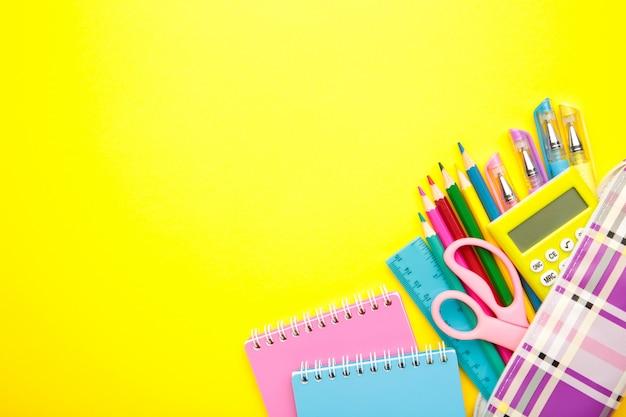 Schulmaterial auf gelb mit kopierraum.