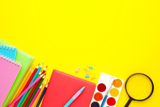 Schulmaterial auf gelbem hintergrund mit kopienraum. zurück zur schule. flach liegen.