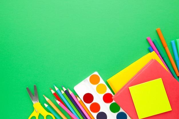 Schulmaterial auf grün mit kopierraum.