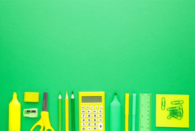 Schulmaterial auf grünem hintergrund mit kopienraum. zurück zur schule. flach liegen.