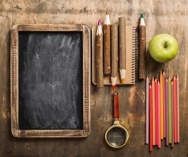 Schulmaterial auf holzhintergrund. flaches layout.