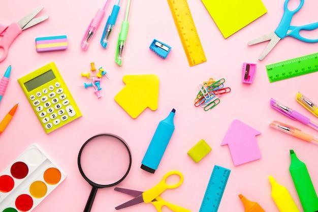 Schulmaterial auf rosa hintergrund. zurück zur schule. flach liegen. minimalismus