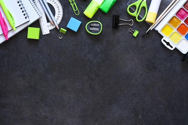 Schulmaterial auf schwarzem hintergrund. zurück zum schulkonzept. flache zusammensetzung mit schulbriefpapier.