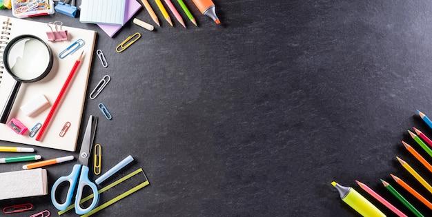 Schulmaterial auf schwarzem rückenbrett