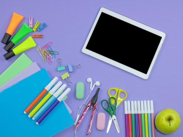 Schulmaterial auf violettem hintergrund
