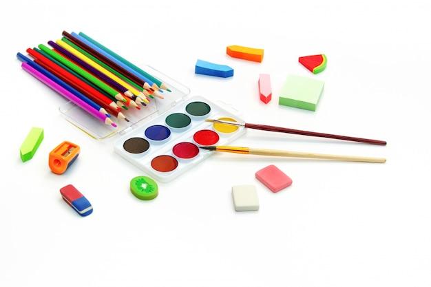 Schulmaterial. farbstifte, farbige büroklammern, farbige farben mit pinseln, radiergummis auf weiß kopieren sie platz.