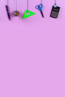 Schulmaterial hängt am seil. schulmaterial auf lila. zurück zum schulkonzept