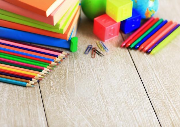 Schulmaterial liegt auf dem holzboden.