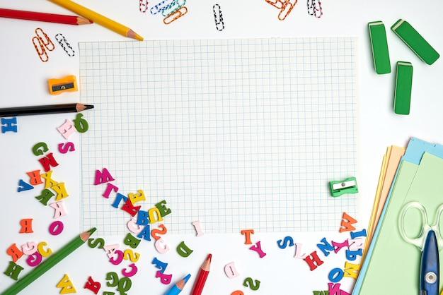 Schulmaterial: mehrfarbige holzstifte, notizbuch, farbiges papier und leeres weißes blatt