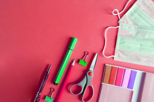 Schulmaterial mit medizinischer gesichtsmaske auf rot