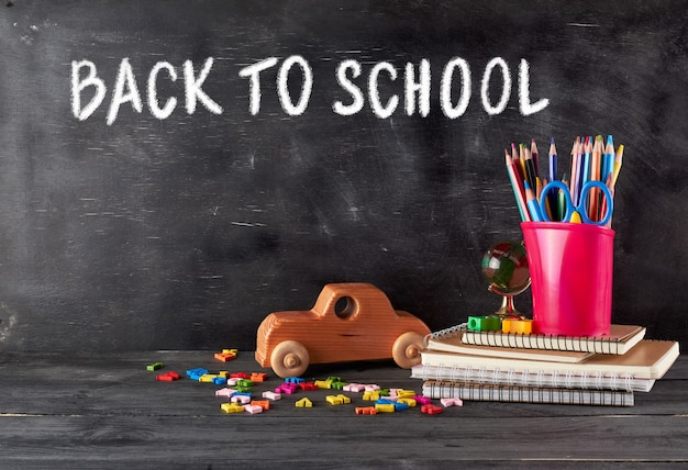 Schulmaterial: notizbuch, bleistifte, schere und ein hölzernes retro-spielzeugauto