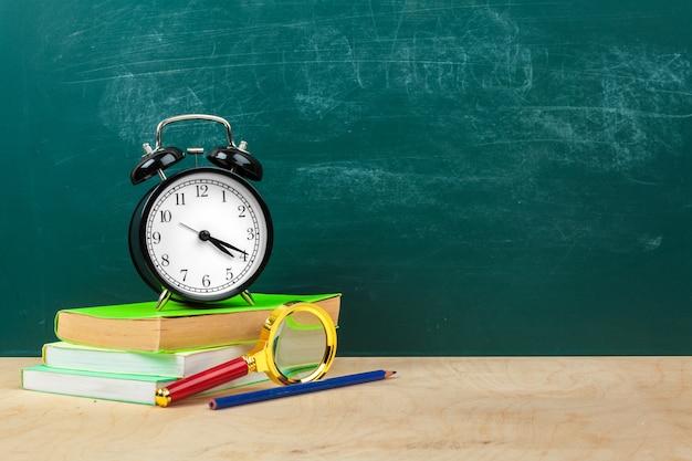 Schulmaterial. schreibgeräte und wecker. zeit, konzept zu studieren