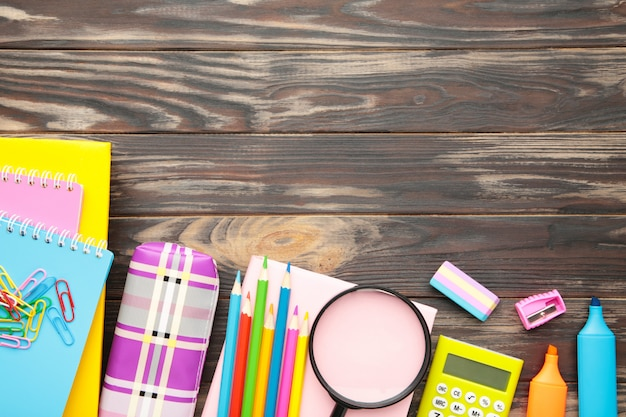 Schulmaterial, schreibwarenzubehör mit kopienraum auf braunem hölzernem hintergrund. flache lage, draufsicht