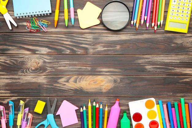 Schulmaterial, schreibwarenzubehör mit kopienraum auf grauem hölzernem hintergrund. flache lage, draufsicht