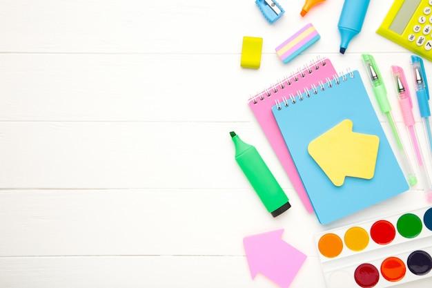 Schulmaterial, schreibwarenzubehör mit kopienraum auf weißem hölzernem hintergrund. flache lage, draufsicht
