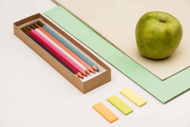 Schulmaterial und apfel auf weißem tisch