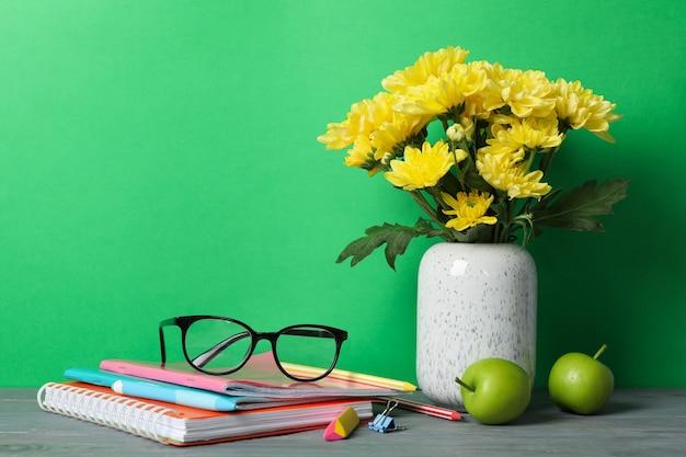 Schulmaterial und blumen gegen grün