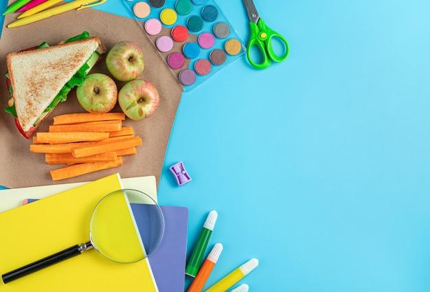 Schulmaterial und ein schulessen aus einem sandwich mit äpfeln und karotten auf blauem hintergrund