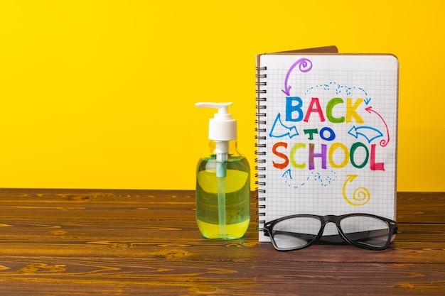 Schulmaterial und händedesinfektionsmittel auf dem schreibtisch. pandemie bildungskonzept