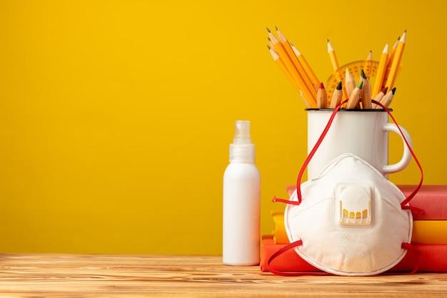 Schulmaterial und medizinische gesichtsmaske auf dem schreibtisch, kopierraum