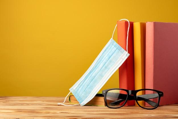Schulmaterial und medizinische gesichtsmaske auf dem schreibtisch