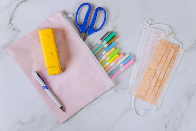 Schulmaterial und schützende gesichtsmaske
