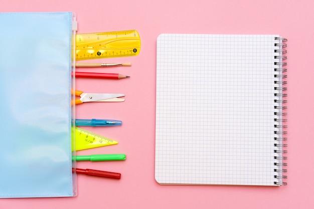 Schulnotizbuch und verschiedene büroartikel zurück zum schulkonzept auf hellrosa hintergrund