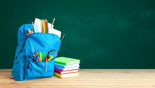 Schulranzen. rucksack mit schulmaterial auf dem hintergrund der grünen tafel. kopieren sie platz für text.
