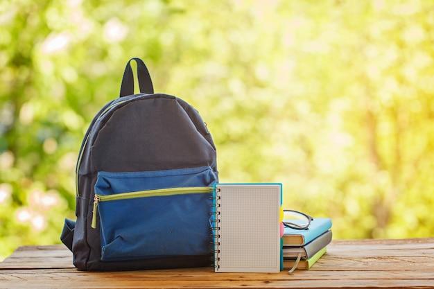 Schulrucksack mit büchern auf holztisch- und naturhintergrund