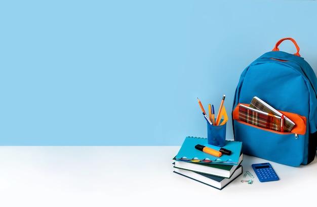 Schulrucksack mit buntem schulmaterial auf blauem hintergrund mit kopienraum. banner-design