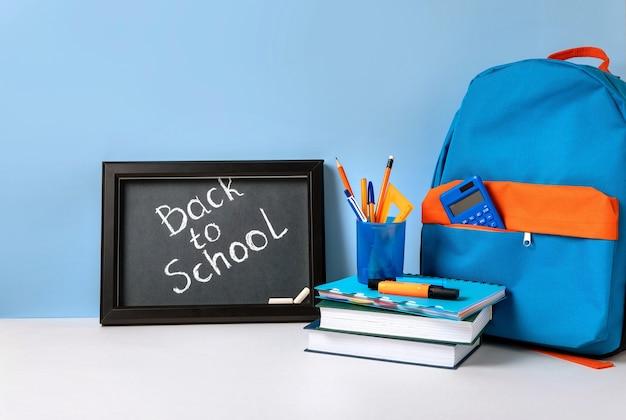 Schulrucksack mit buntem schulmaterial und tafel mit briefen zurück zur schule. schulbedarf auf blauem hintergrund. banner-design