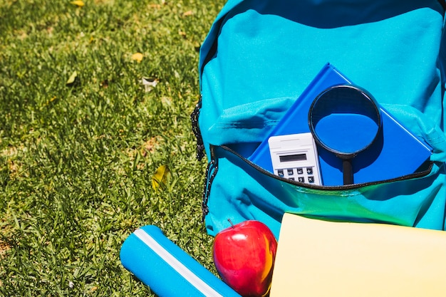 Schulrucksack mit schulmaterial auf gras