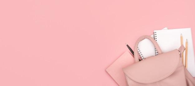 Schulrucksack und büromaterial auf pink. speicherplatz kopieren.
