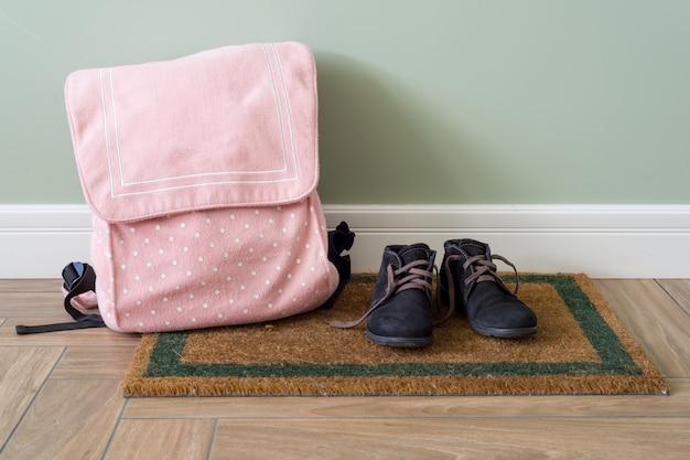 Schulrucksack und stiefel auf dem boden