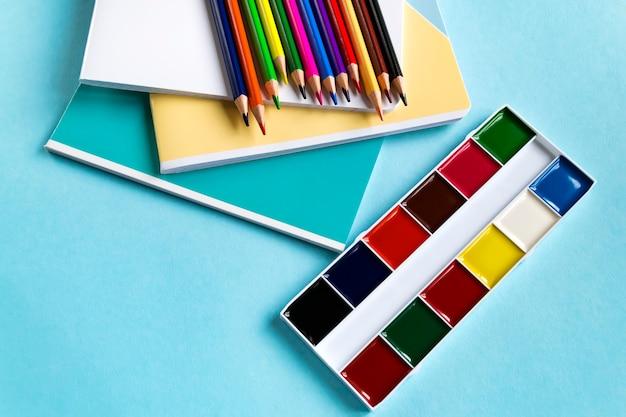 Schulsatz notizbücher, farbige bleistifte und aquarelle auf einem blauen hintergrund mit kopienraum. ansicht von oben